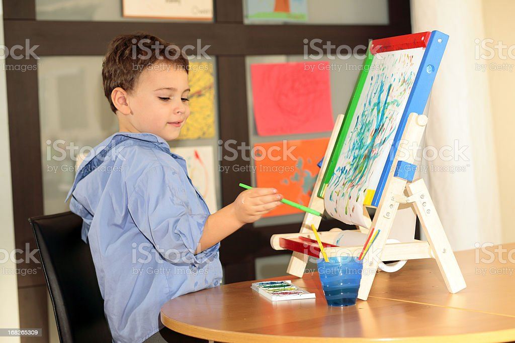Autistic child painting with easel stock photo