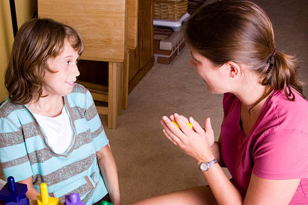 Autistic girl getting praise during therapy stock photo