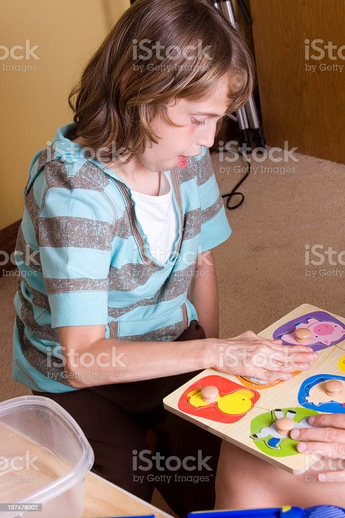 Autistic girl working on puzzle royalty-free stock photo