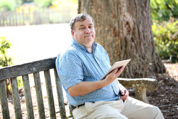Autistic man outdoors Autistic man outdoors using a phone and tablet. learning difficulty stock pictures, royalty-free photos & images