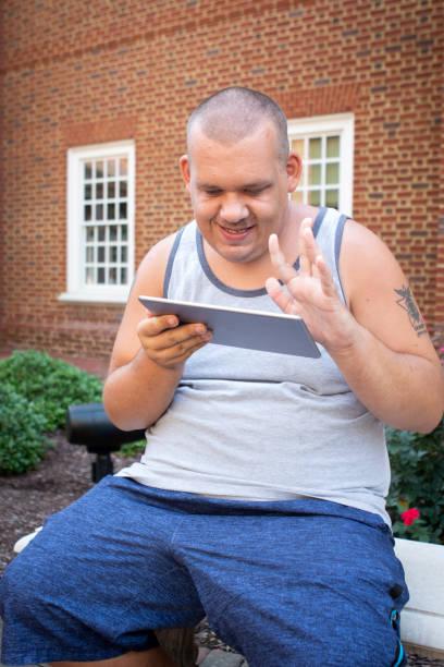 autistischer mann mit tablet - autismus stock-fotos und bilder
