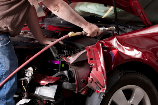 Closeup photo of an auto body mechanic using a compressed air wrench to remove the side fender from a vehicle that was in an auto accident.