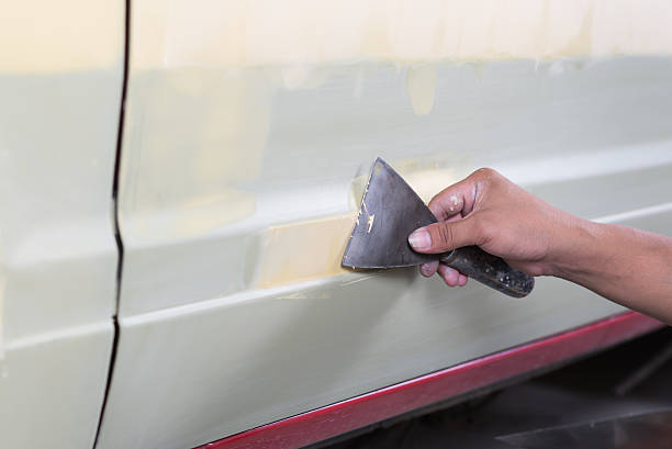 Auto body repair seires : Working on putty filler stock photo