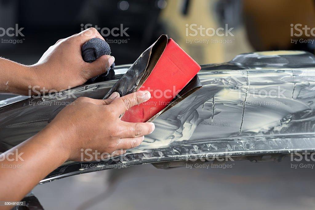 Auto body repair series : Sanding bumper stock photo