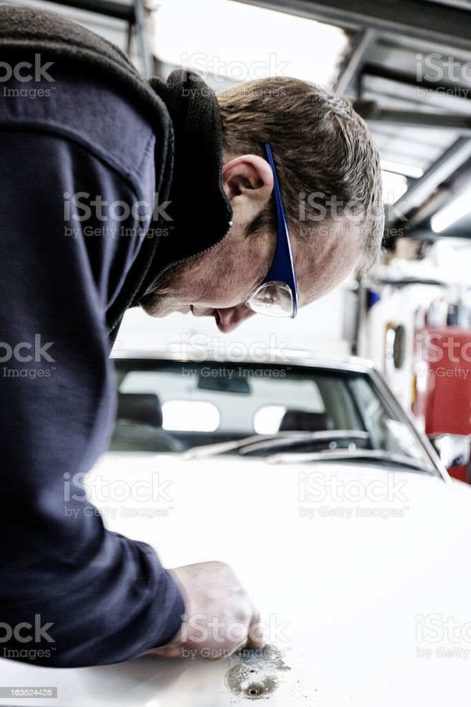 Auto body technician examining damage on a car royalty-free stock photo