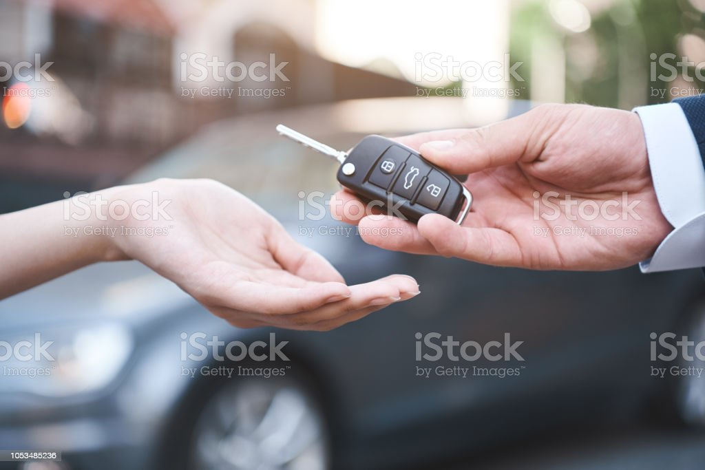 auto business, car sale, transportation, people and ownership co auto business, car sale, transportation, people and ownership concept - close up of car salesman giving key to new owner or customer over auto show background Adult Stock Photo