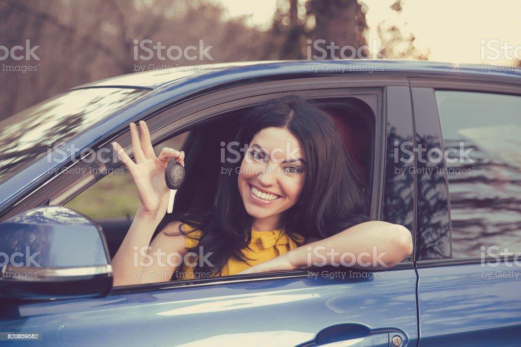 Auto business, sale, consumerism concept. Happy woman showing new car key stock photo