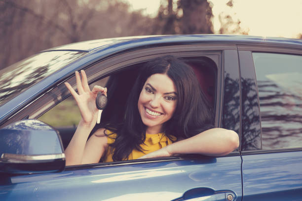 Auto business, sale, consumerism concept. Happy woman showing new car key stock photo