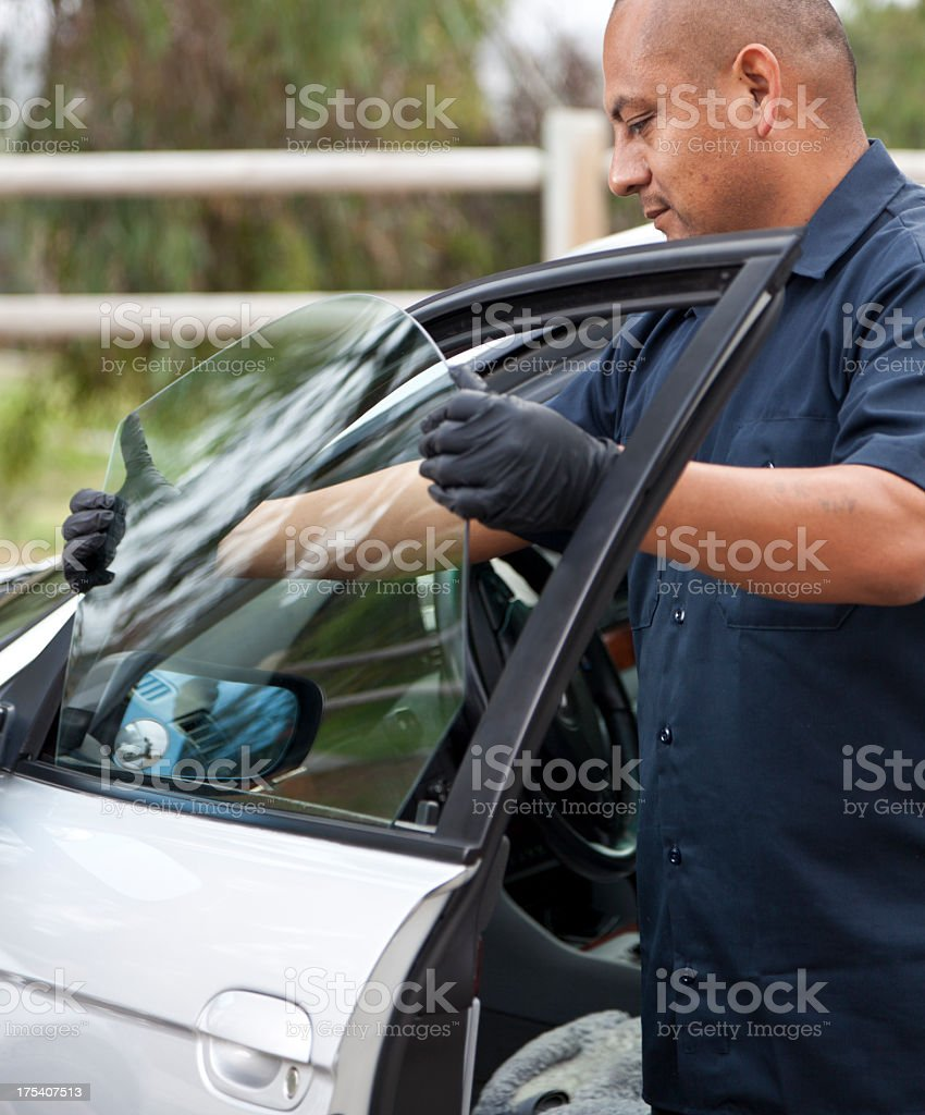 Man repairing and replacing the glass on a car.