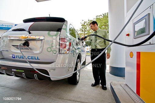 A driver at a hydrogen pump at a Los Angeles gas station refuels a futuristic, zero-emission Chevrolet Equinox hydrogen fuel cell powered automobile. The vehicle has a range of 150 miles. An electronic plug-in cable controls the refilling process.