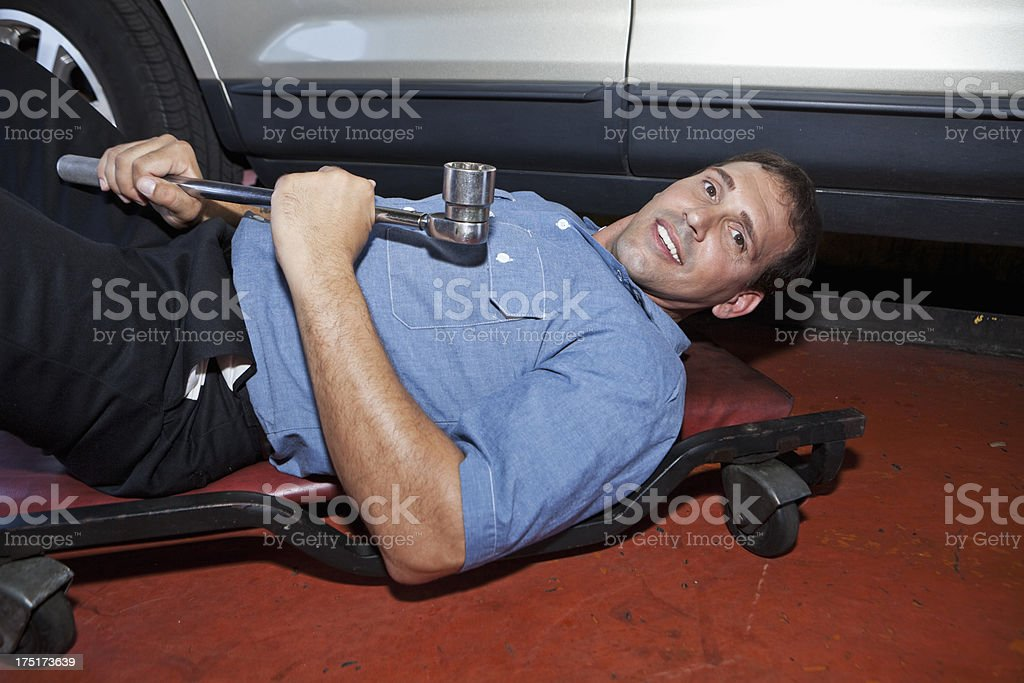 Auto mechanic about to work under car stock photo