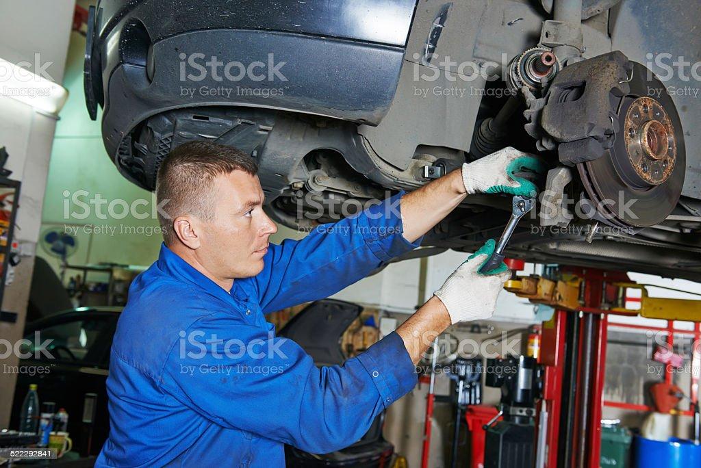 auto mechanic at car suspension repairing stock photo