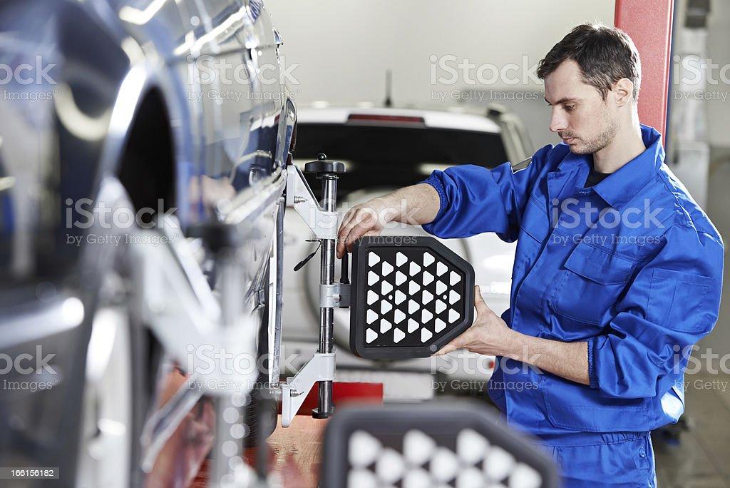 auto mechanic at wheel alignment work with sensor stock photo