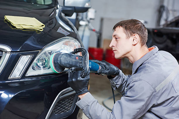 auto mechanic buffing and polishing car headlight Auto body repairs. Mechanic worker burnish and polishing automobile car headlight by buffing grinding machine in garage workshop. Toned headlight stock pictures, royalty-free photos & images