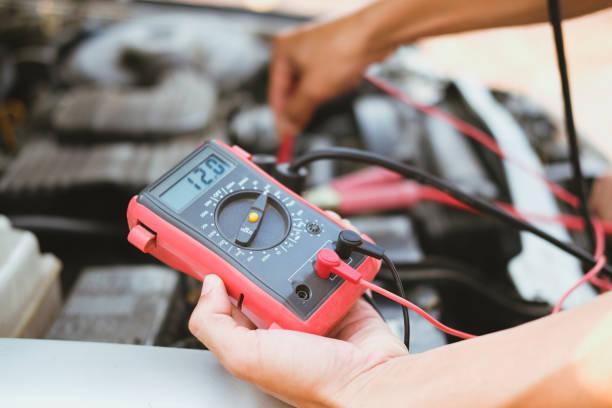 Kfz-Mechaniker überprüfen die Batteriespannung des Autos um Voltmeter Multimeter – Foto