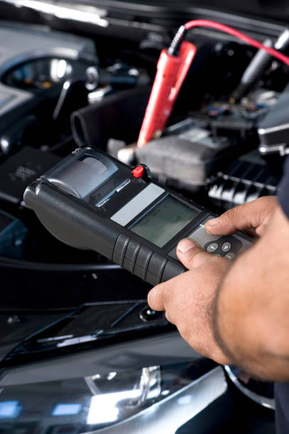 Auto mechanic checking car battery stock photo