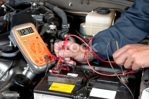 istock Auto mechanic checking car battery voltage 106539729