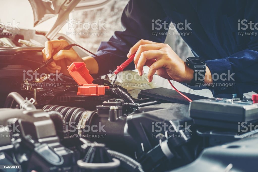 Auto mechanic checking car battery voltage - foto stock