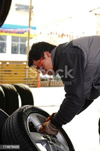 898487280 istock photo Auto mechanic checking new tires 174979405