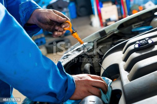 istock Auto mechanic checking the oil dipstick under a cars hood 464178779