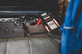 istock Auto mechanic checks car battery status. Checking the vehicle electrical system concept 1254065786