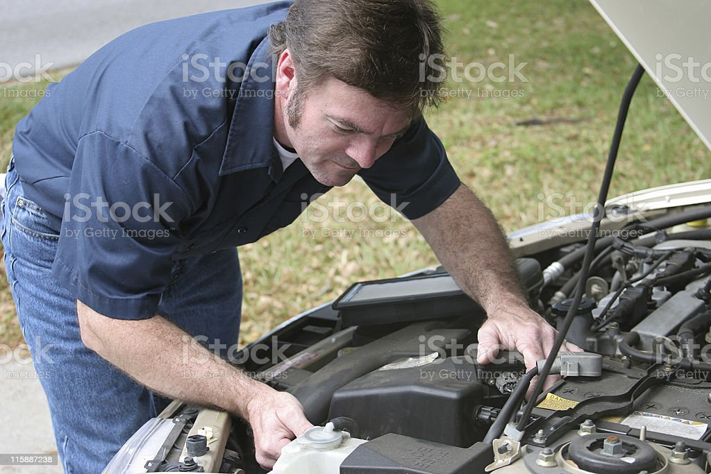 Auto Mechanic Checks Engine An attractive, friendly auto mechanic checking the engine of a car. Horizontal.   Photo taken as work was actually being performed. Adult Stock Photo
