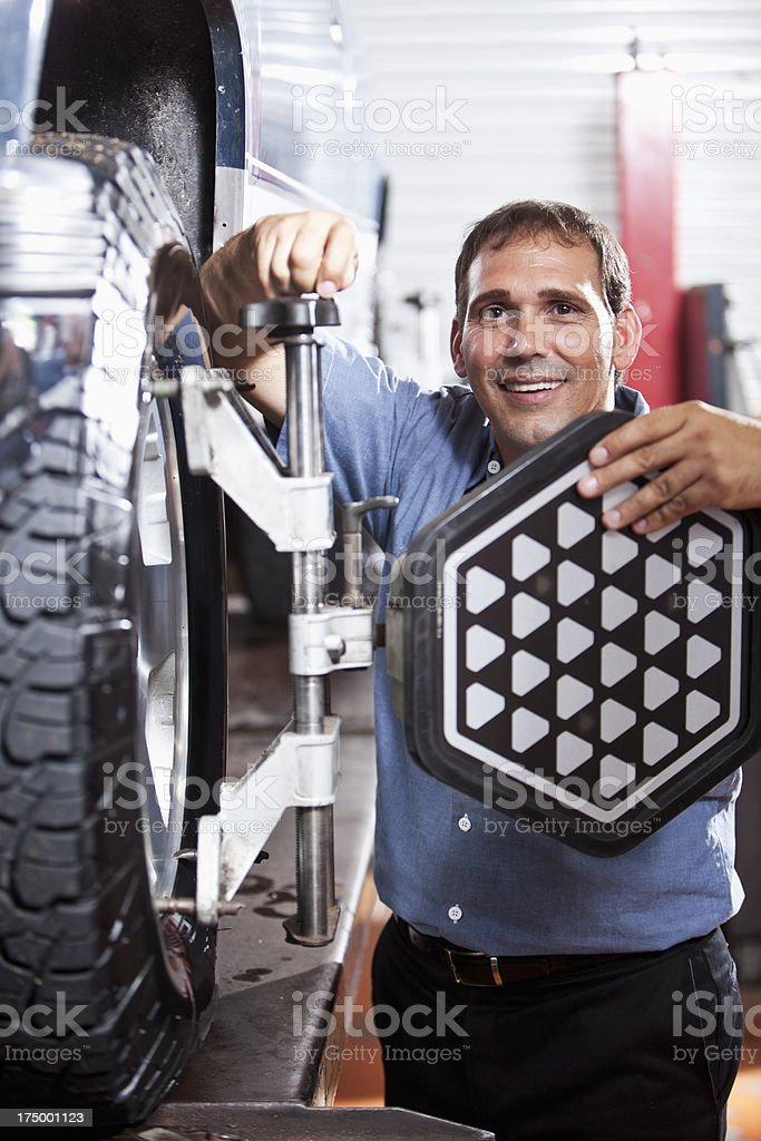 Auto mechanic doing wheel alignment royalty-free stock photo