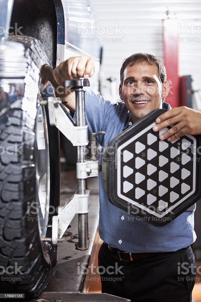 Auto mechanic doing wheel alignment stock photo