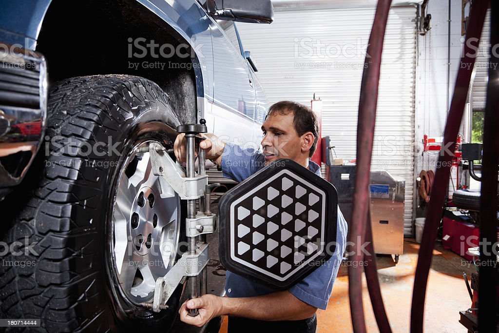Auto mechanic doing wheel alignment stock photo