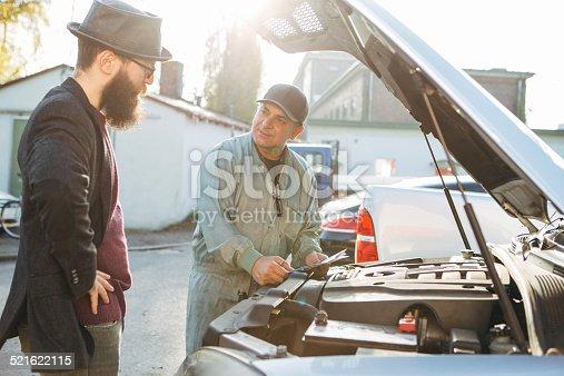 136591855 istock photo auto mechanic gives an advice to customer 521622115