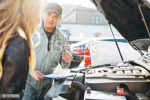 136591855 istock photo auto mechanic gives an advice to female customer 521578259