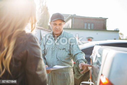 136591855 istock photo auto mechanic gives an advice to female customer 521621849