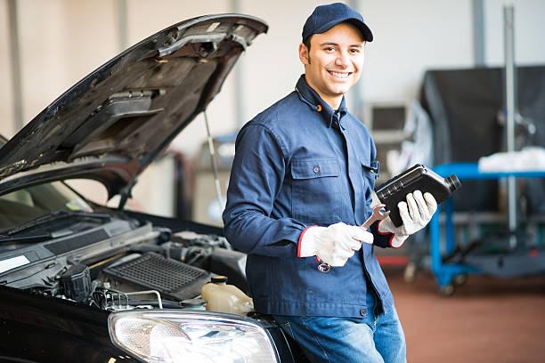 Auto mechanic holding a jug of motor oil stock photo