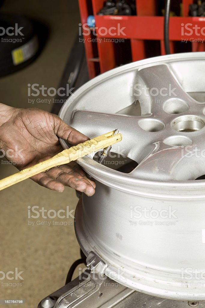 Auto Mechanic Installing new Valve Stem on an Aluminum Rim royalty-free stock photo