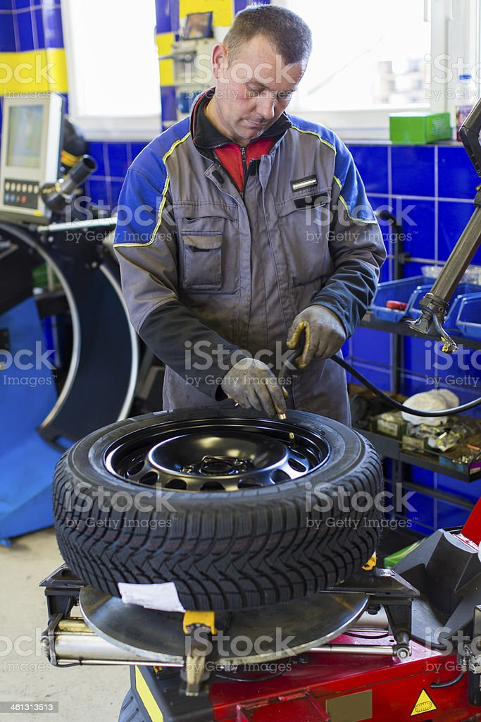 Auto mechanic is changin tire...prepairing car for winter royalty-free stock photo