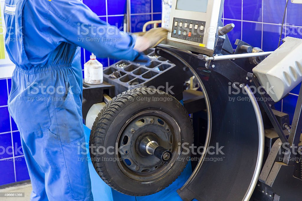 Auto mechanic is changin tire...prepairing car for winter stock photo