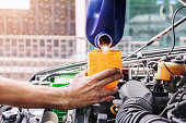 istock Auto mechanic is filling up the car's engine oil. 1278039670