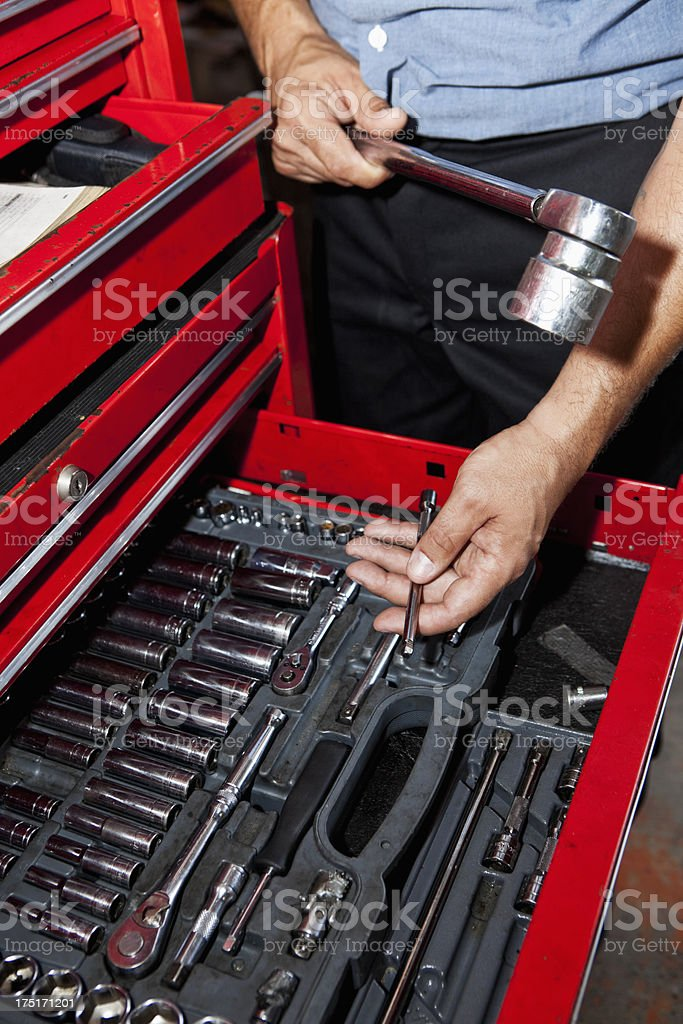 Auto mechanic looking in toolbox stock photo
