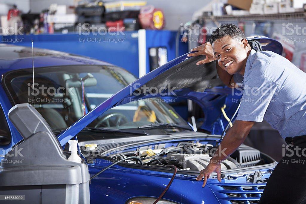 Auto mechanic looking under car hood stock photo