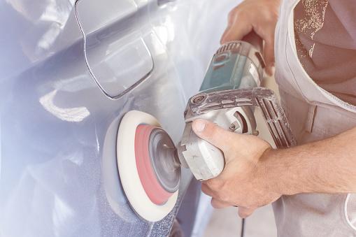 istock Auto mechanic makes car body polishing. The concept of automotive business 950446438