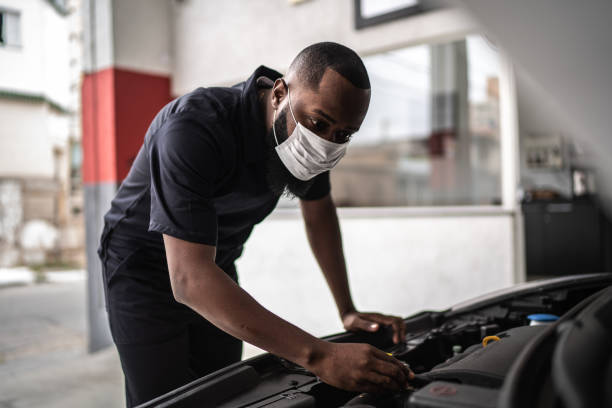 auto mechanic man with face mask working at auto repair shop - afro latino mask imagens e fotografias de stock