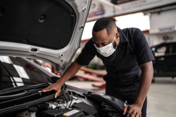 Auto mechanic man with face mask working at auto repair shop stock photo