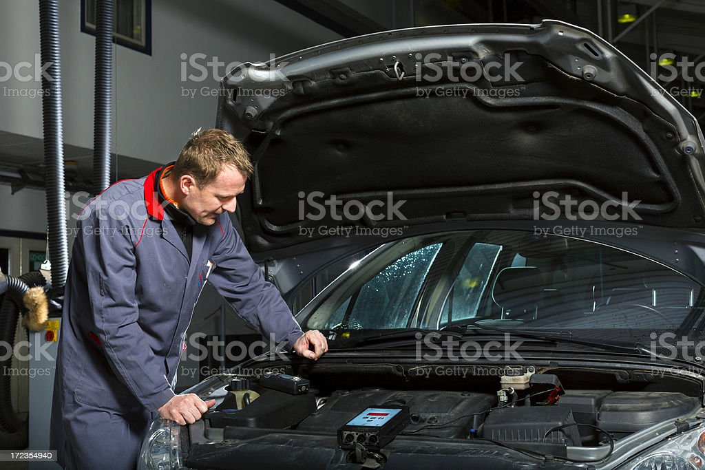 Auto mechanic measuring car engine royalty-free stock photo