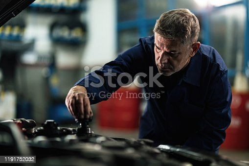 Mid adult mechanic checking car coolant system and opening radiator cap in a garage.