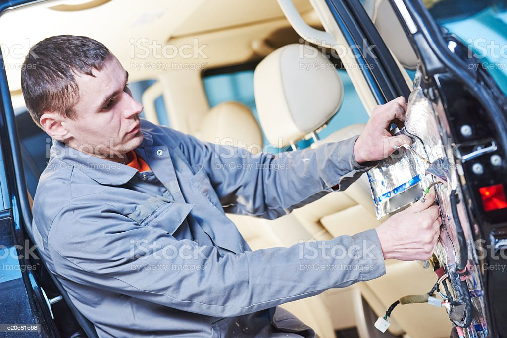 auto mechanic placing the damping mats on car door stock photo