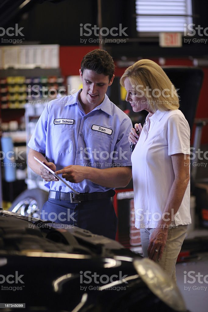 Auto mechanic pointing on his tablet to a customer stock photo