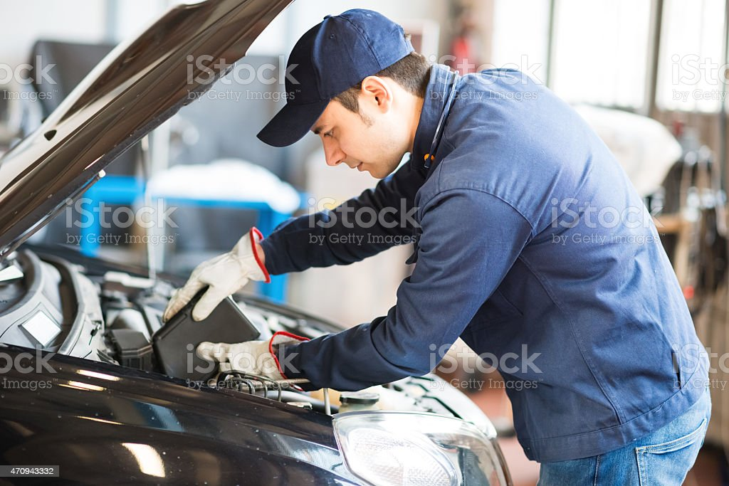 Auto mechanic putting oil in a car engine stock photo