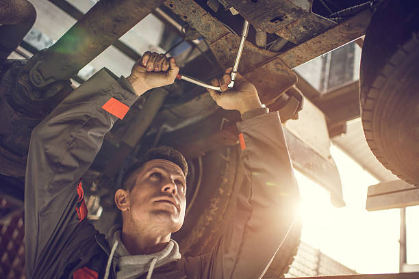 Auto mechanic repairing a chassis of a truck. Mid adult mechanic using socket wrench while working on a chassis of a truck. socket wrench stock pictures, royalty-free photos & images