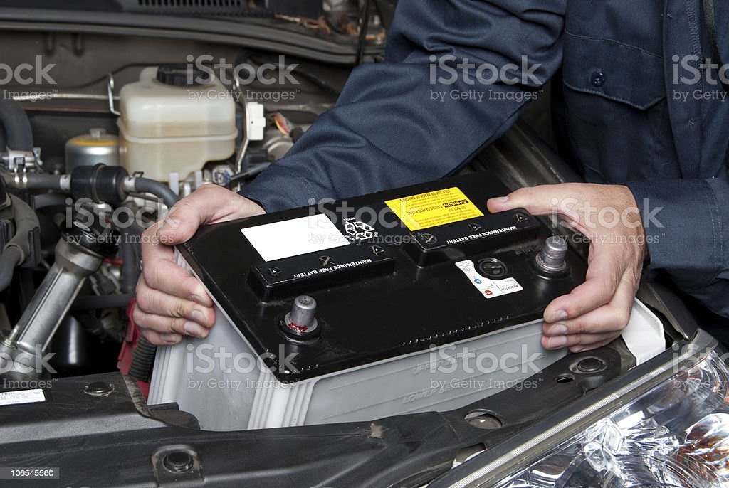 Auto mechanic replacing car battery stock photo
