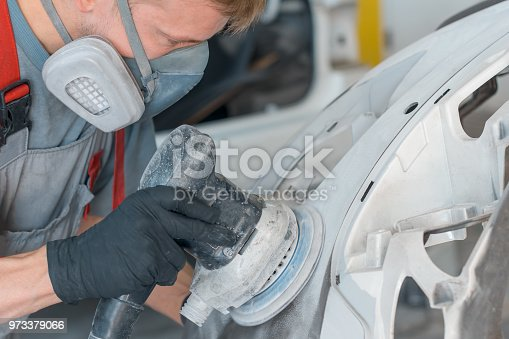 istock Auto mechanic restores car body part after car accident 973379066